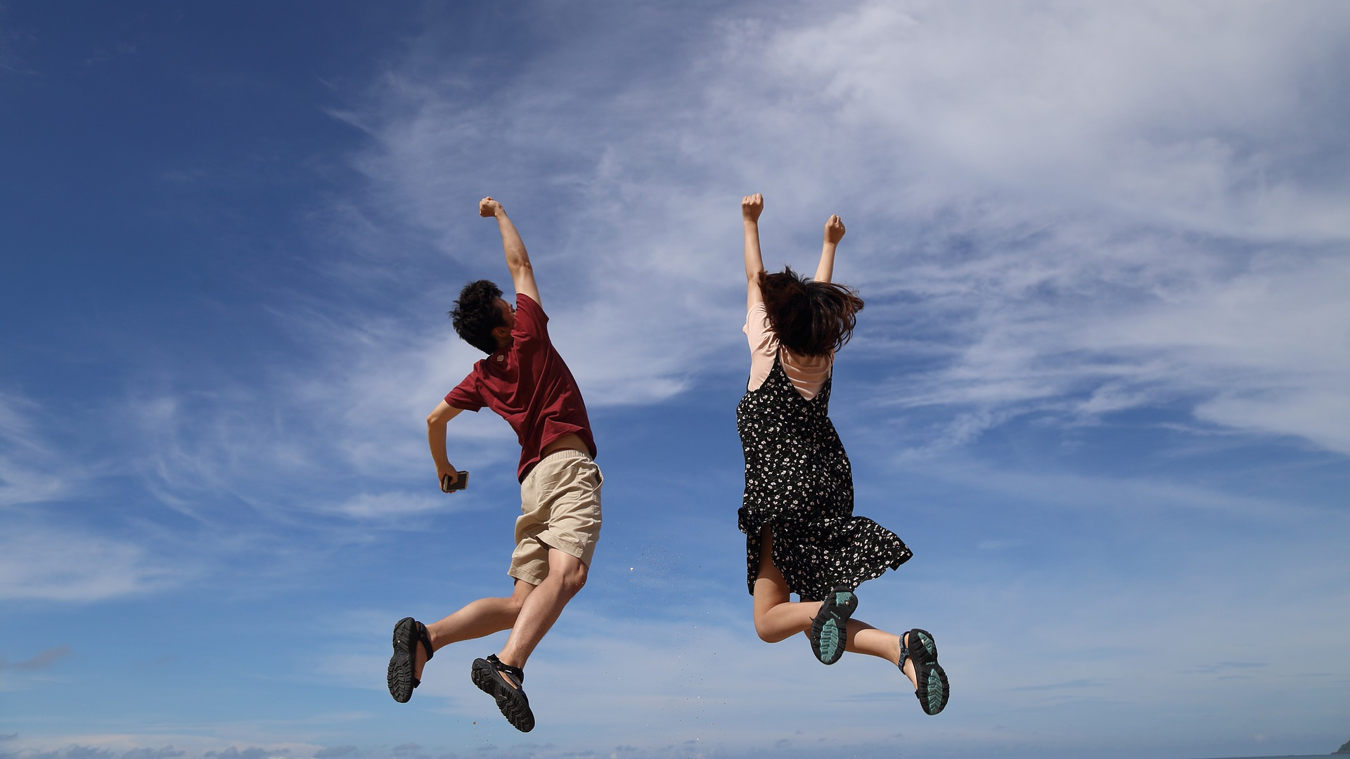 A man and a woman jump triumphantly into the air against a blue sky with wispy white clouds.