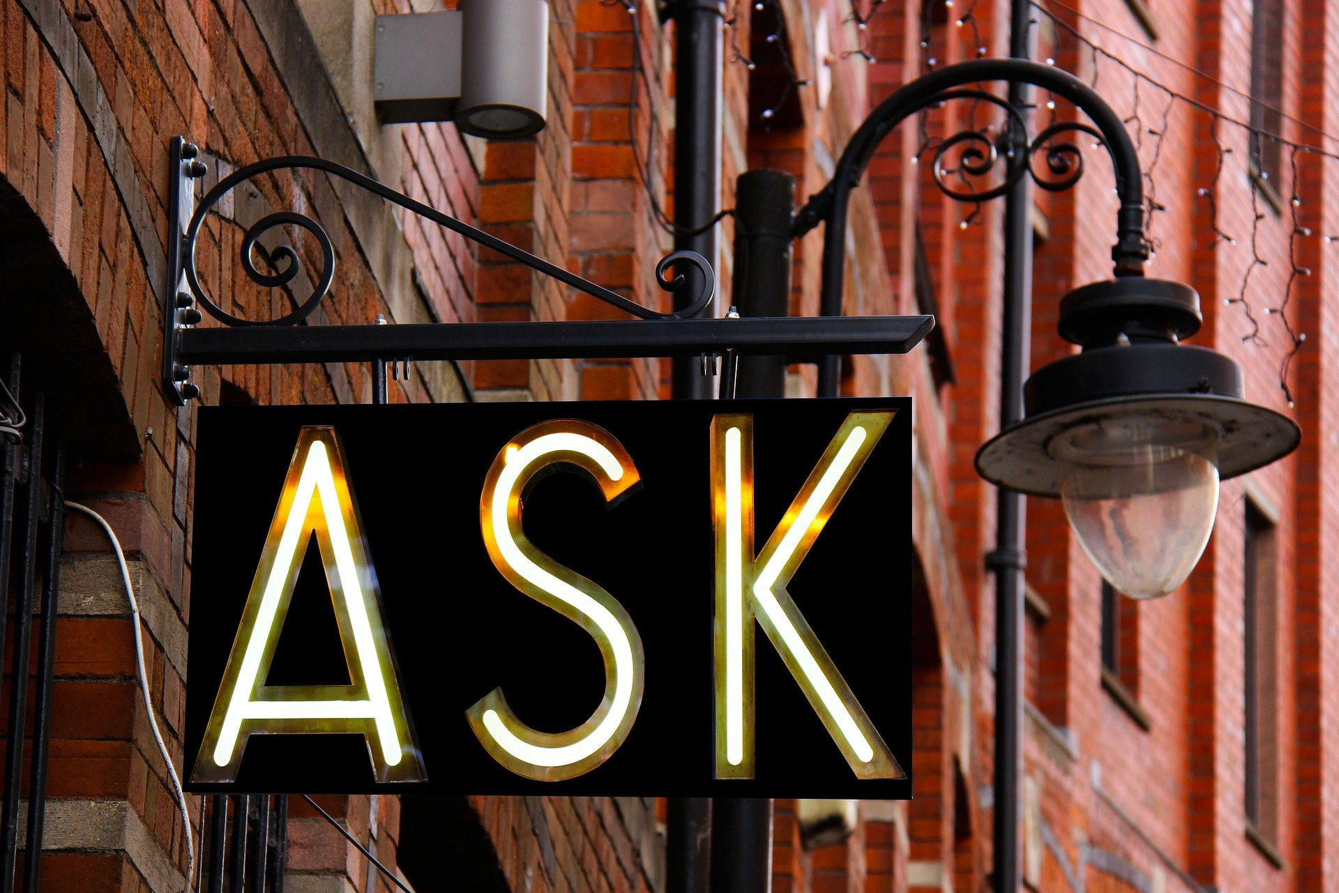 """A light-up sign outside a brick building reads """"Ask."""""""