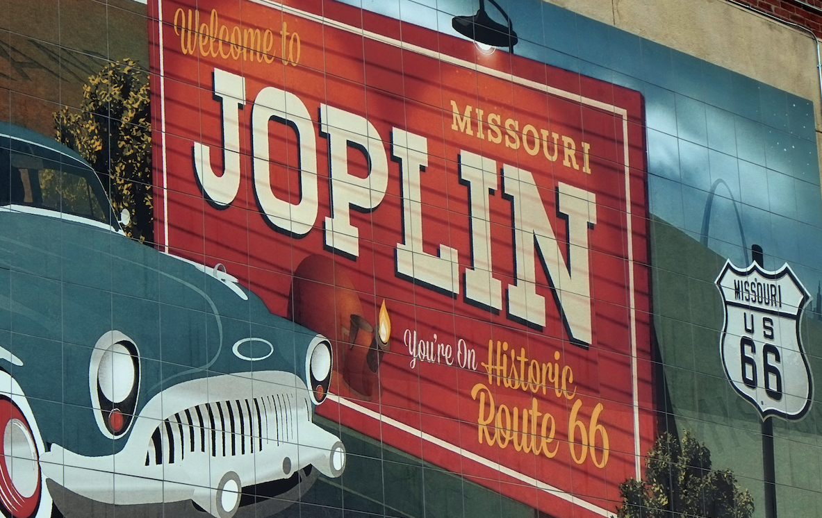 """Photo of a Mural in Joplin Missouri depicting a historic vehicle and a billboard that reads """"Welcome to Joplin Missouri. You're on Historic Route 66"""""""