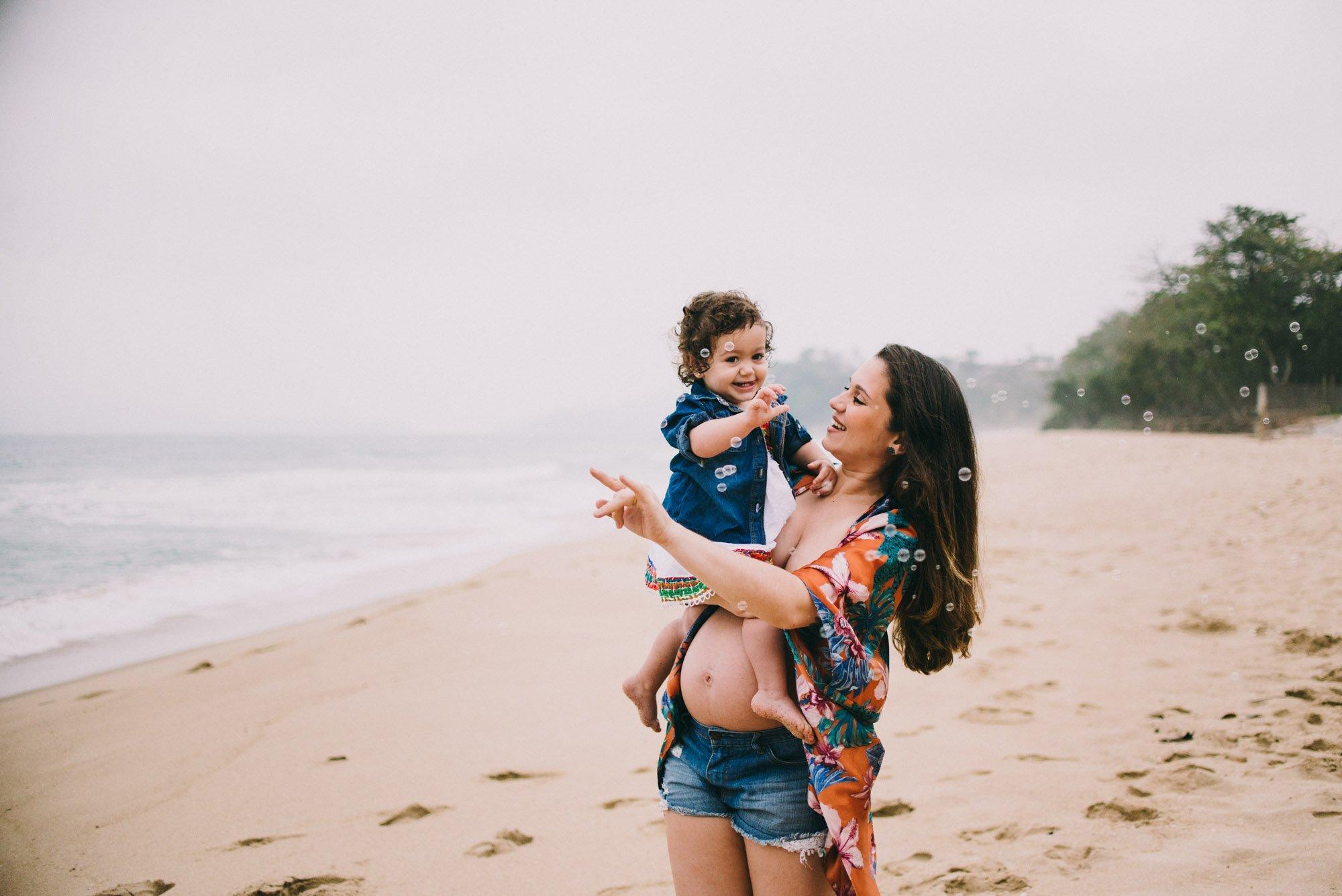 mãe grávida com filha na praia ubatuba
