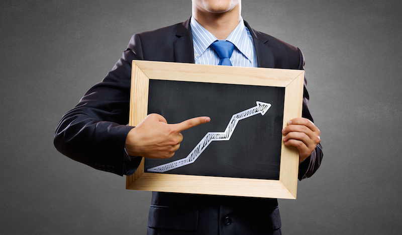 Unrecognizable businessman holding chalkboard with growth arrow concept