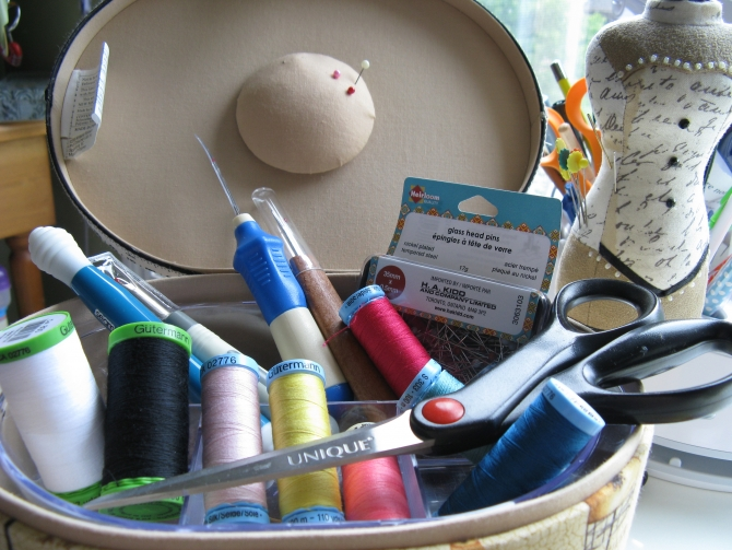A sewing box filled with an assortment of Gutterman thread, Unique sewing tools, scissors, pins, seam rippers.