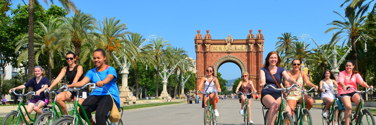 Teenage travelers biking through Barcelona during summer Spanish language immersion program