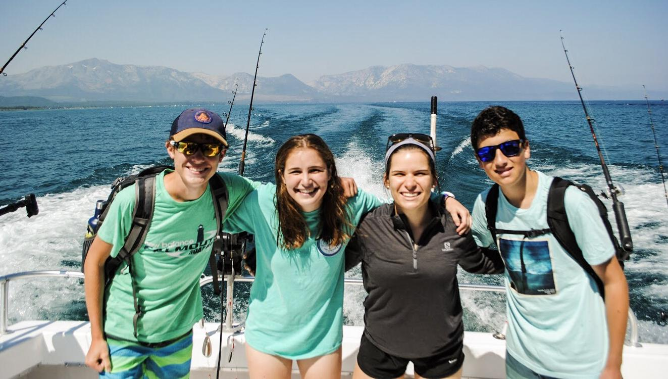 High school students smile on a boat on their summer teen tour through the USA