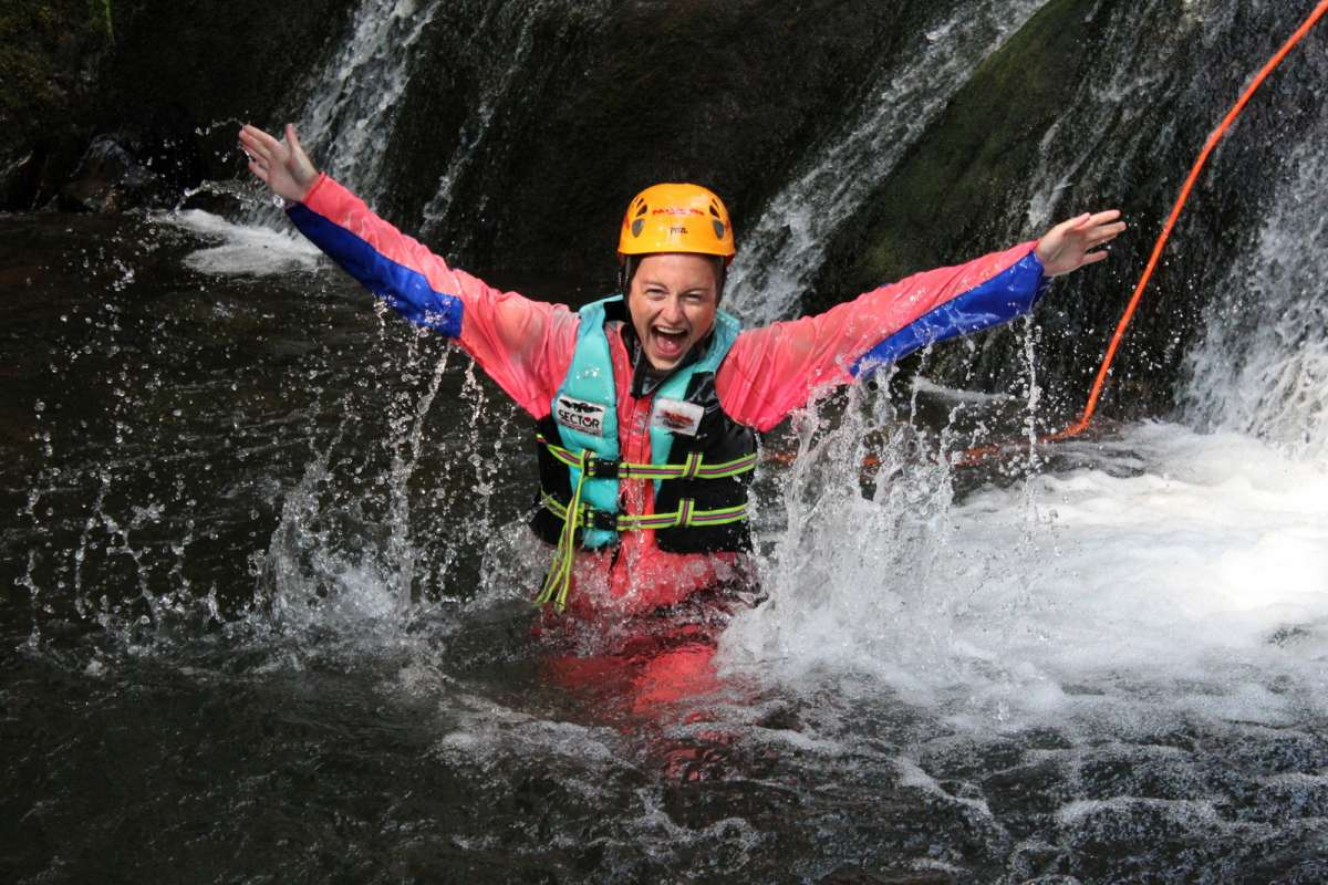 Happy teenage traveler canyoning in Europe on summer adventure program