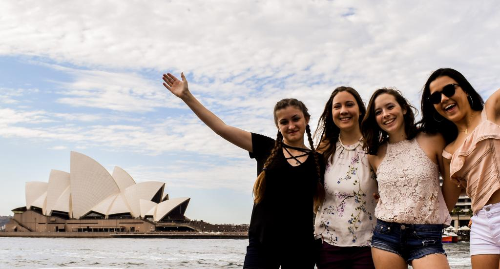 High school students taking pictures in front of the Sydney Opera House on a summer teen tour to Australia.