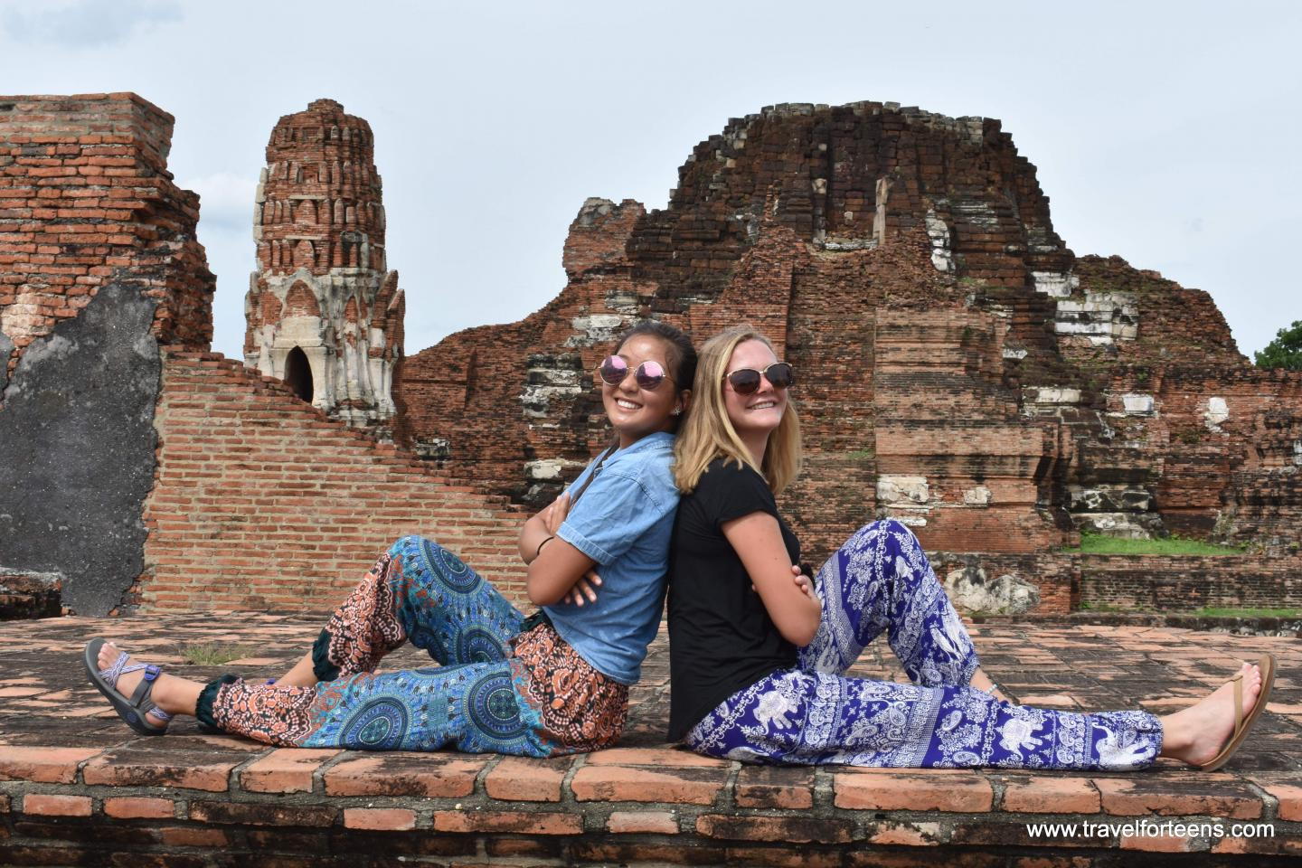 High school students pose in front of a temple on their summer program to Thailand.
