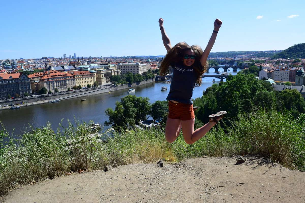 Teen traveler jumping in Prague on summer adventure travel program