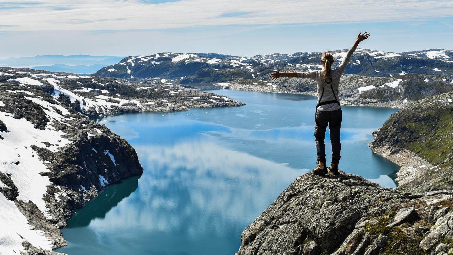 High school student poses on a glacier in Norway on their summer high school program to Scandinavia