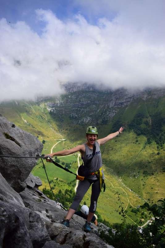 Happy teenage girl rock climbing in Europe adventure program