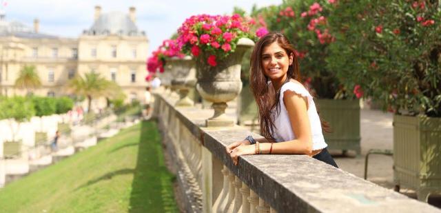 Teenage girl with flowers in Tuileries Gardens Paris on summer program