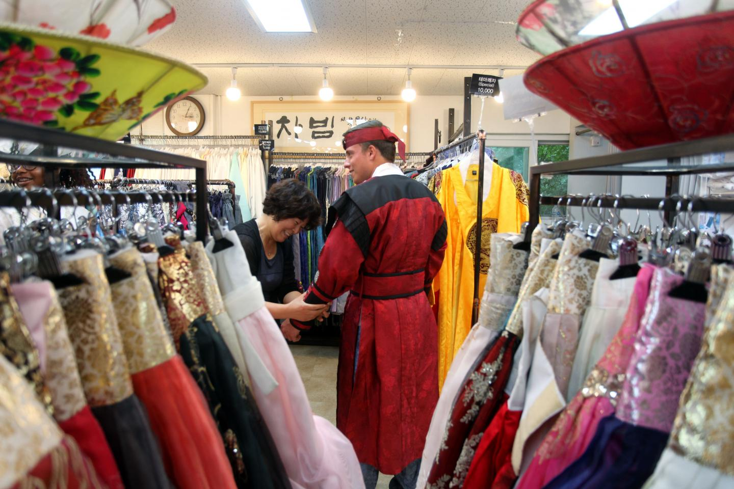Teenage traveler puts on local hanbok outfit during summer youth travel program in South Korea