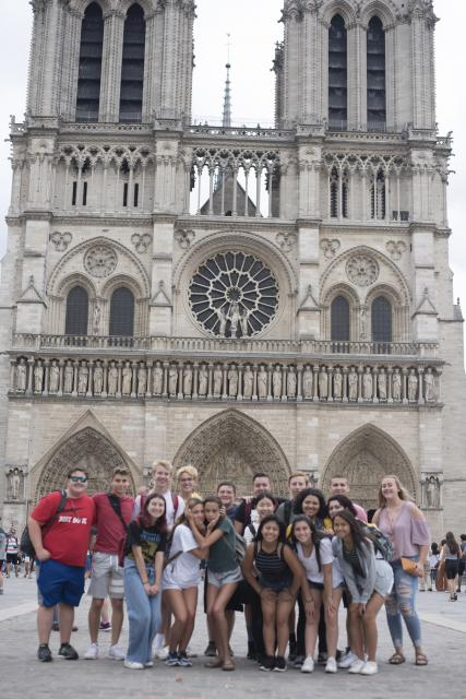 Group of teen travelers visits Notre Dame Cathedral in Paris during summer youth travel program