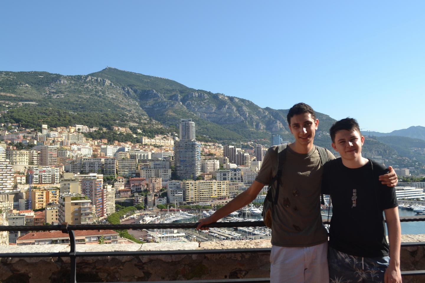 Teenage travelers at Monaco yacht port during summer travel program in French Riviera