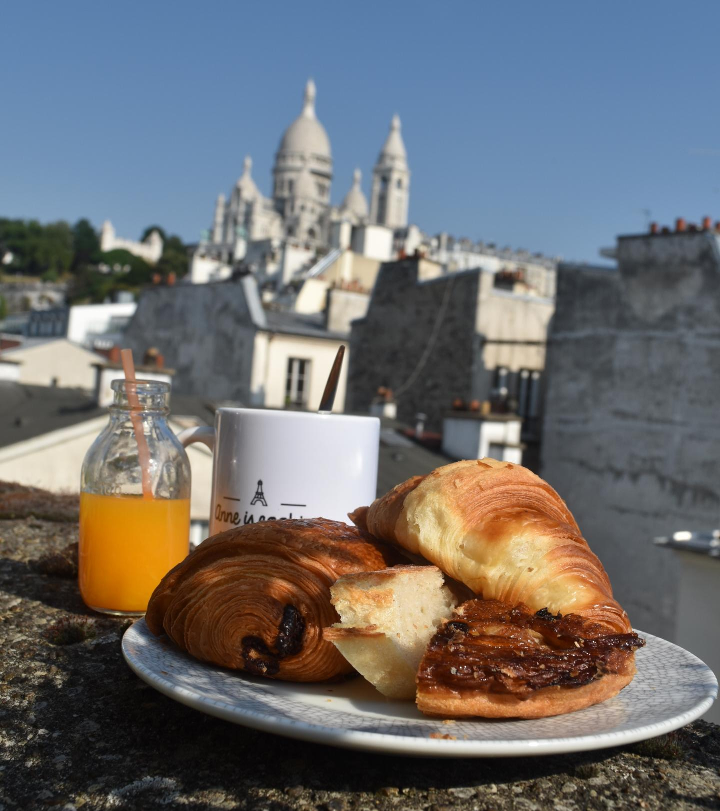 French chocolate pastry croissant with view of Sacre Coeur Basilica in Montmartre seen on summer teen travel program in Paris