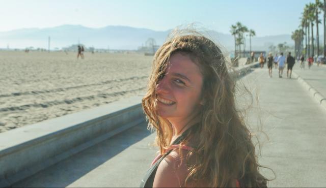 High school teen smiles on the beach on her summer tour.