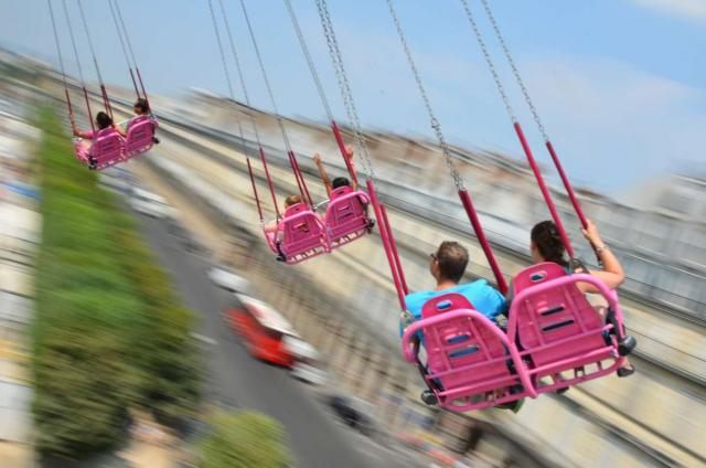 Teen travelers ride attractions in Tuileries Gardens on summer youth program in France