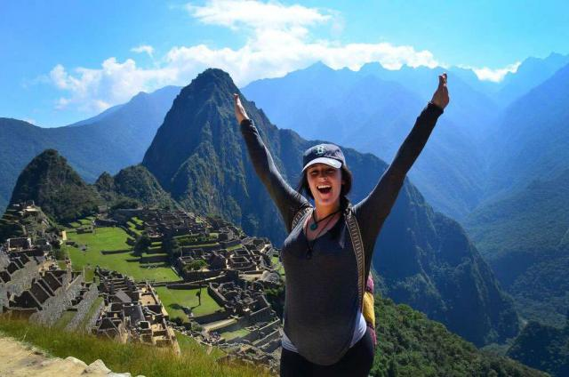 An excited teen celebrates atop Machu Picchu on her summer adventure tour of Peru.