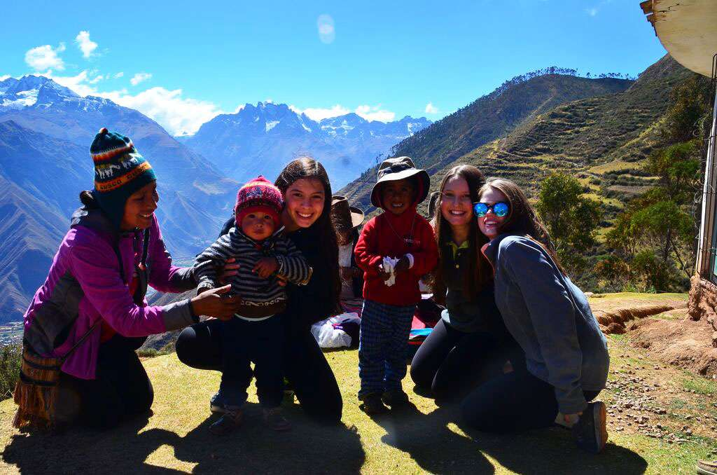 A group of students pose for a picture with local children on their community service program in Peru.