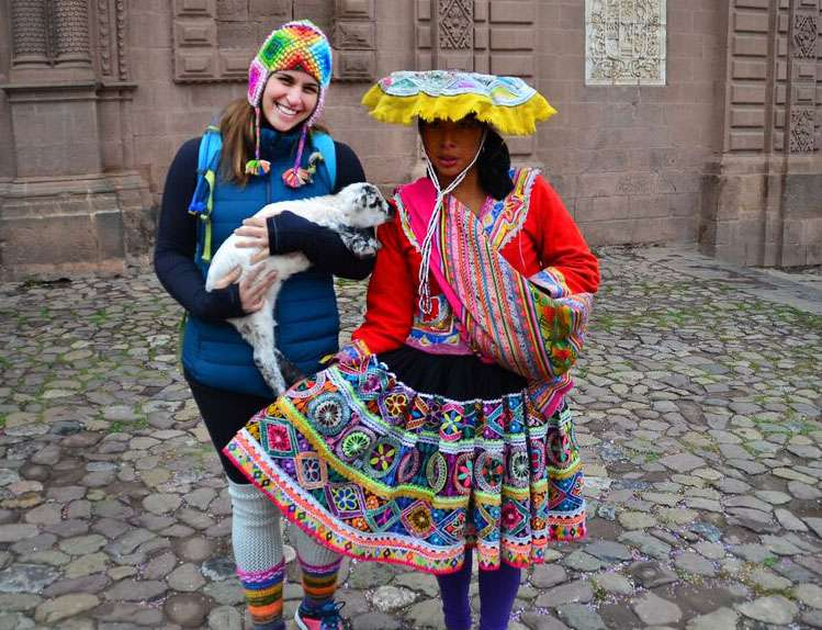 A teen takes a photo with a local and a goat on their summer travel program in Peru.