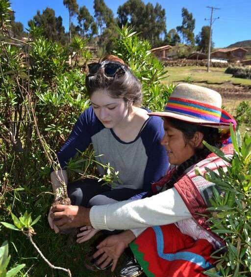 A student works alongside a local on their summer community service program in Peru.