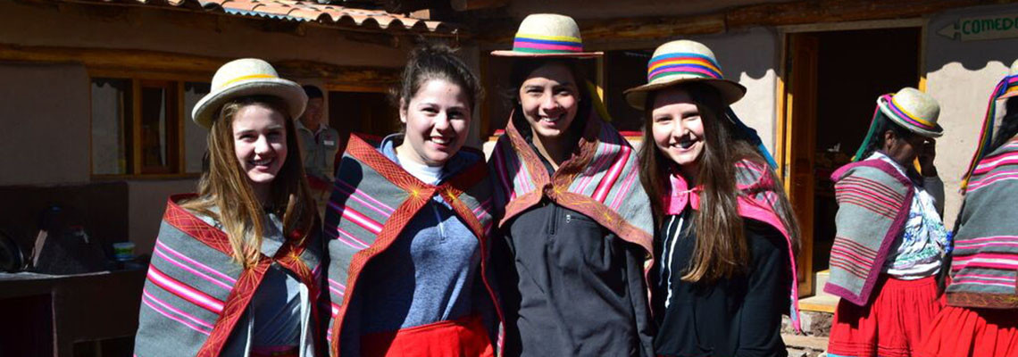 A group of teens wear local clothes on their adventure travel program in Peru.