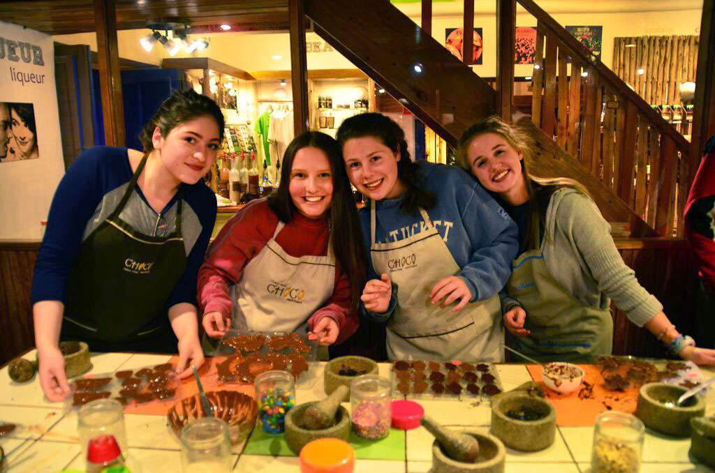 A group of teens learn how to cook local cuisine on their summer student tour of Peru.