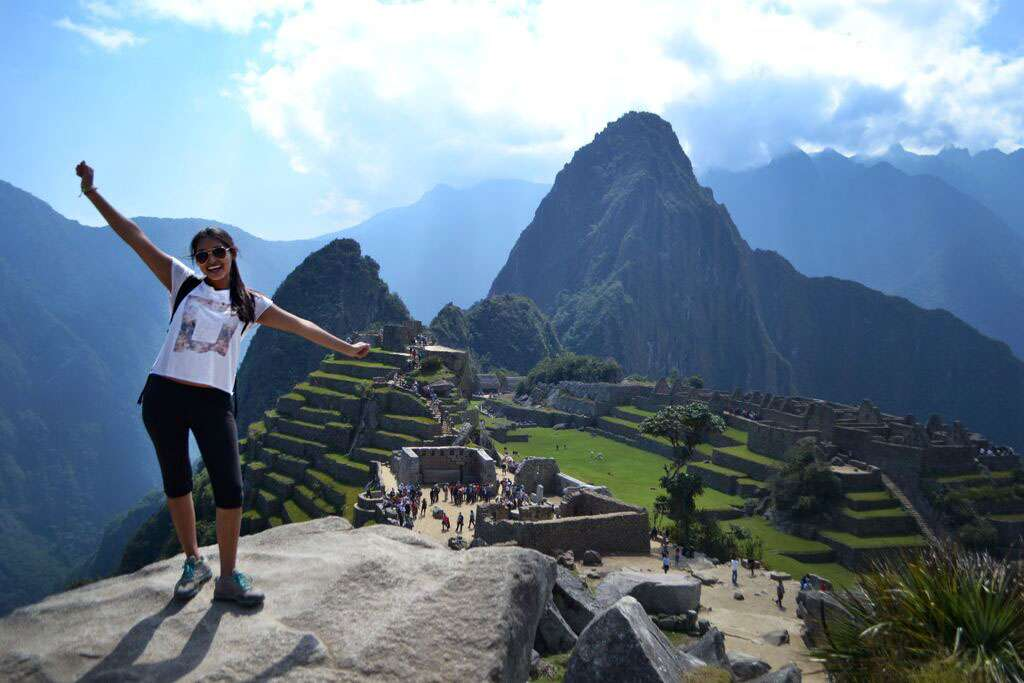 A teen poses in Machu Picchu on her student tour of Peru.