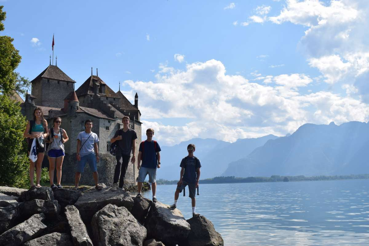 Teens swimming in Switzerland alpine lake on youth travel tour