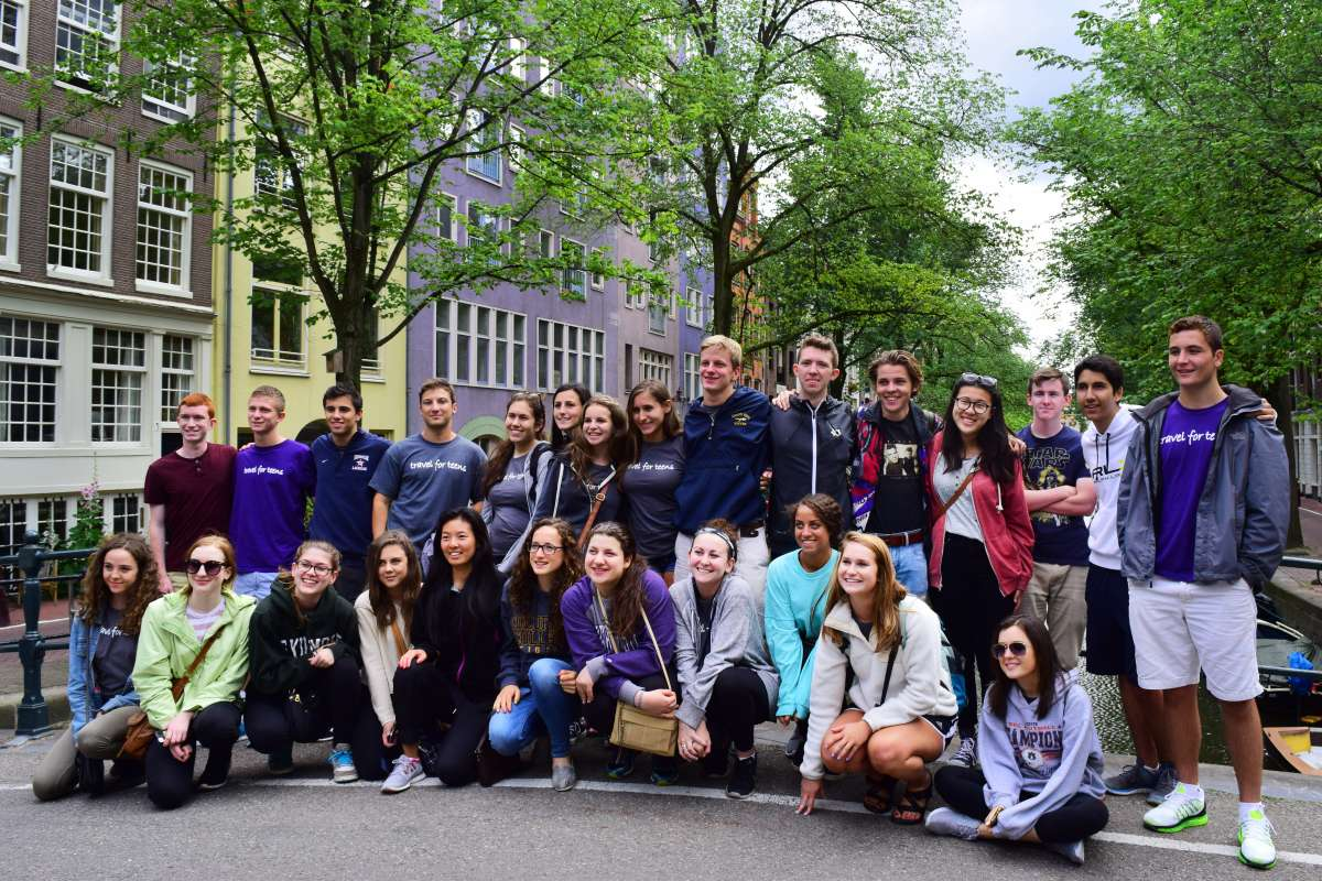 Happy group of teens at Amsterdam canals on summer youth program