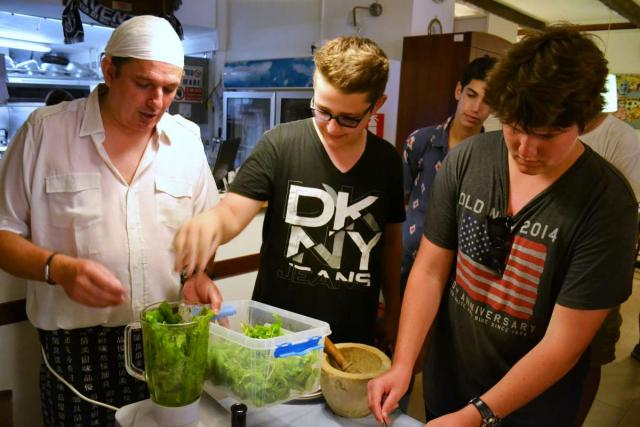 Teenage travelers make pesto during cooking class in Italy on summer youth travel program