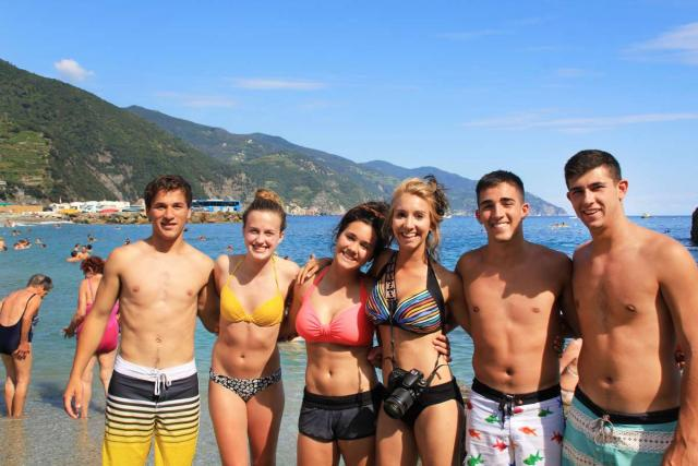 Teenage travelers make friends on Italian beach during summer youth travel program