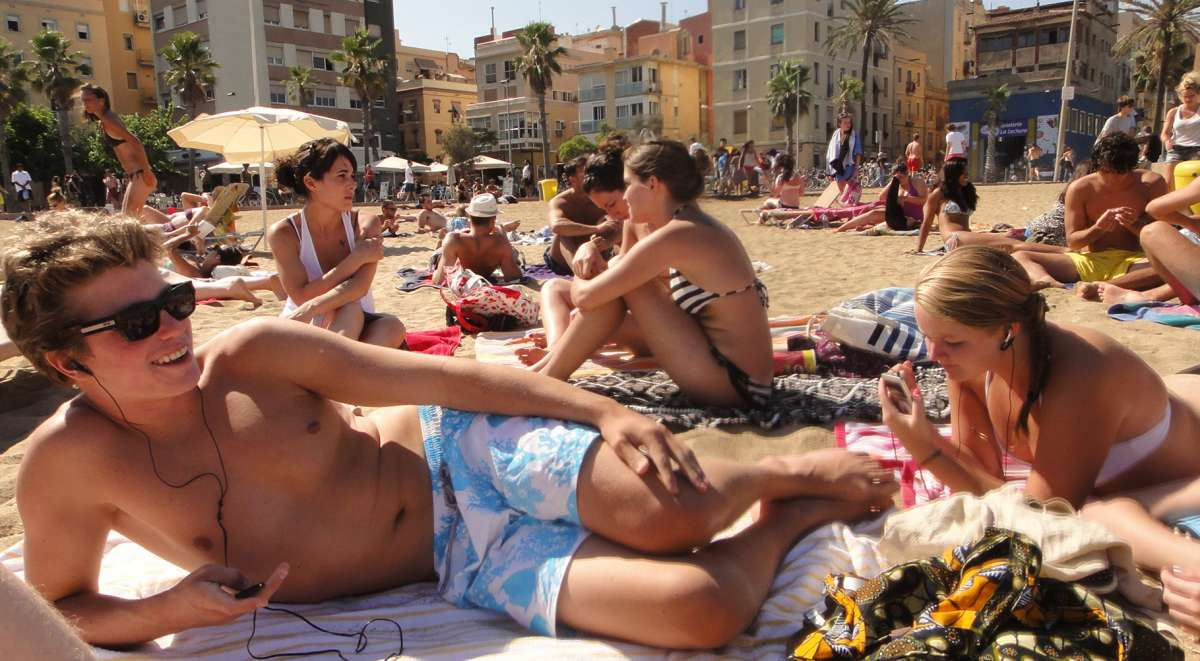Teenage travelers relax on Mediterranean beach on summer youth travel program