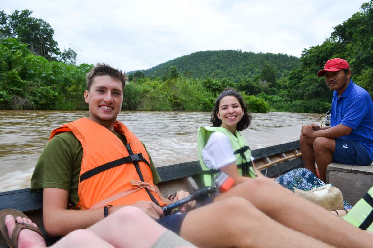 Teenage travelers on boat ride during summer youth travel program in Thailand