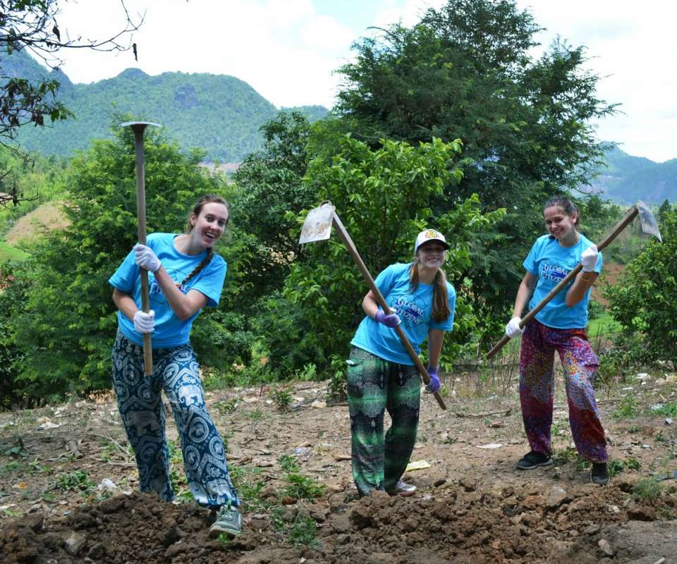 Teenage travelers volunteer on a farm during summer youth travel program in Thailand