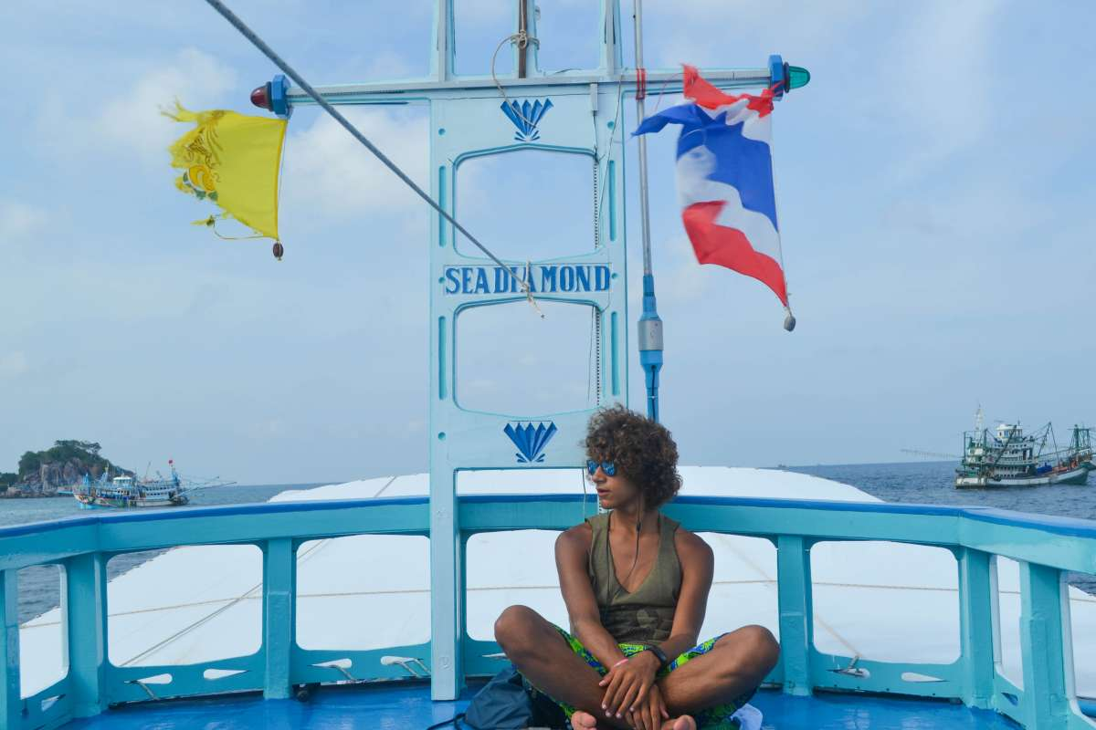 Teenage traveler relaxes during boat cruise during summer youth travel program in Thailand