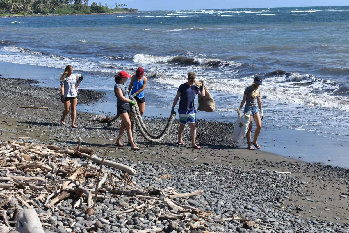 Students clean up a beach in Hawaii on their teen summer service program.