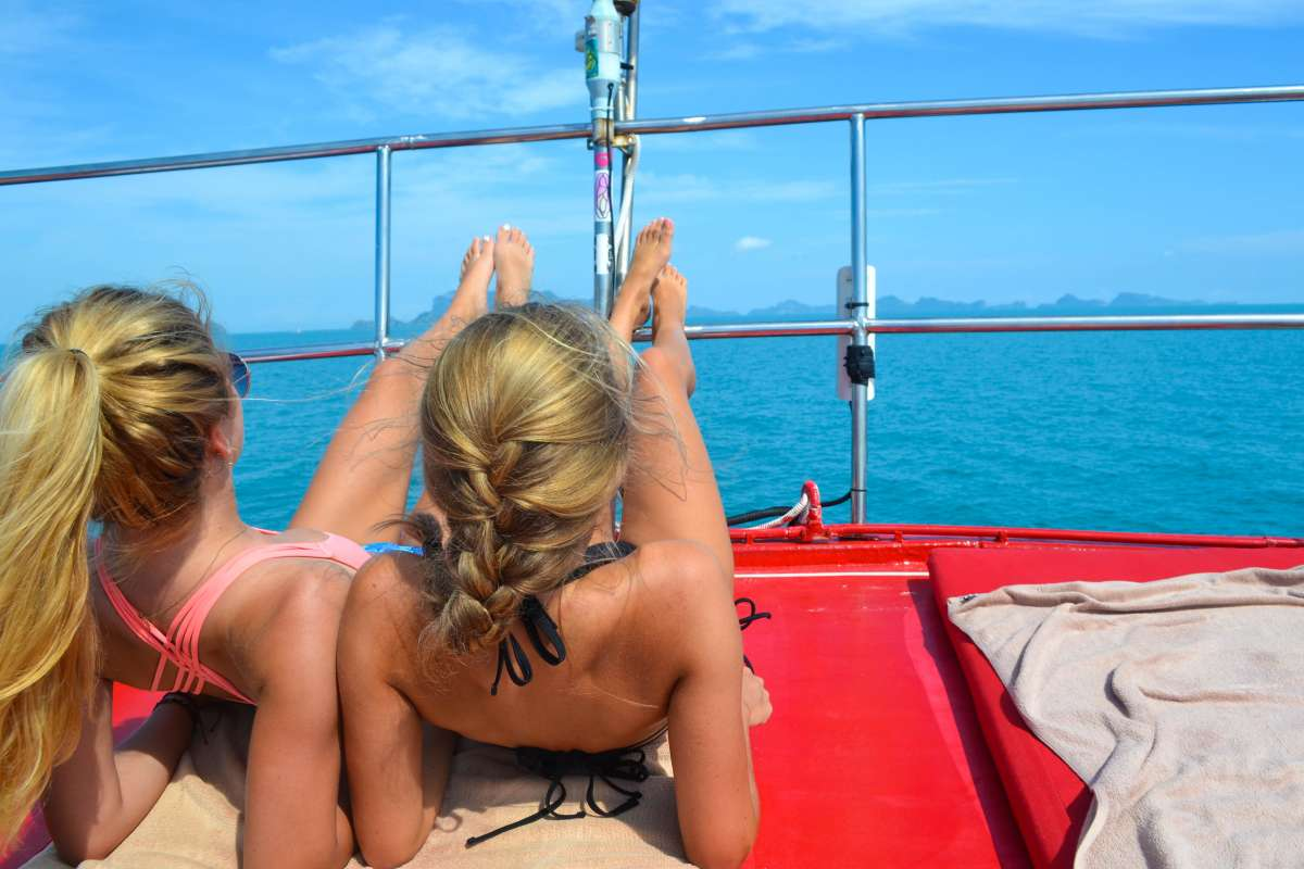 Teenage travelers relax on boat cruise during summer youth travel program in Thailand