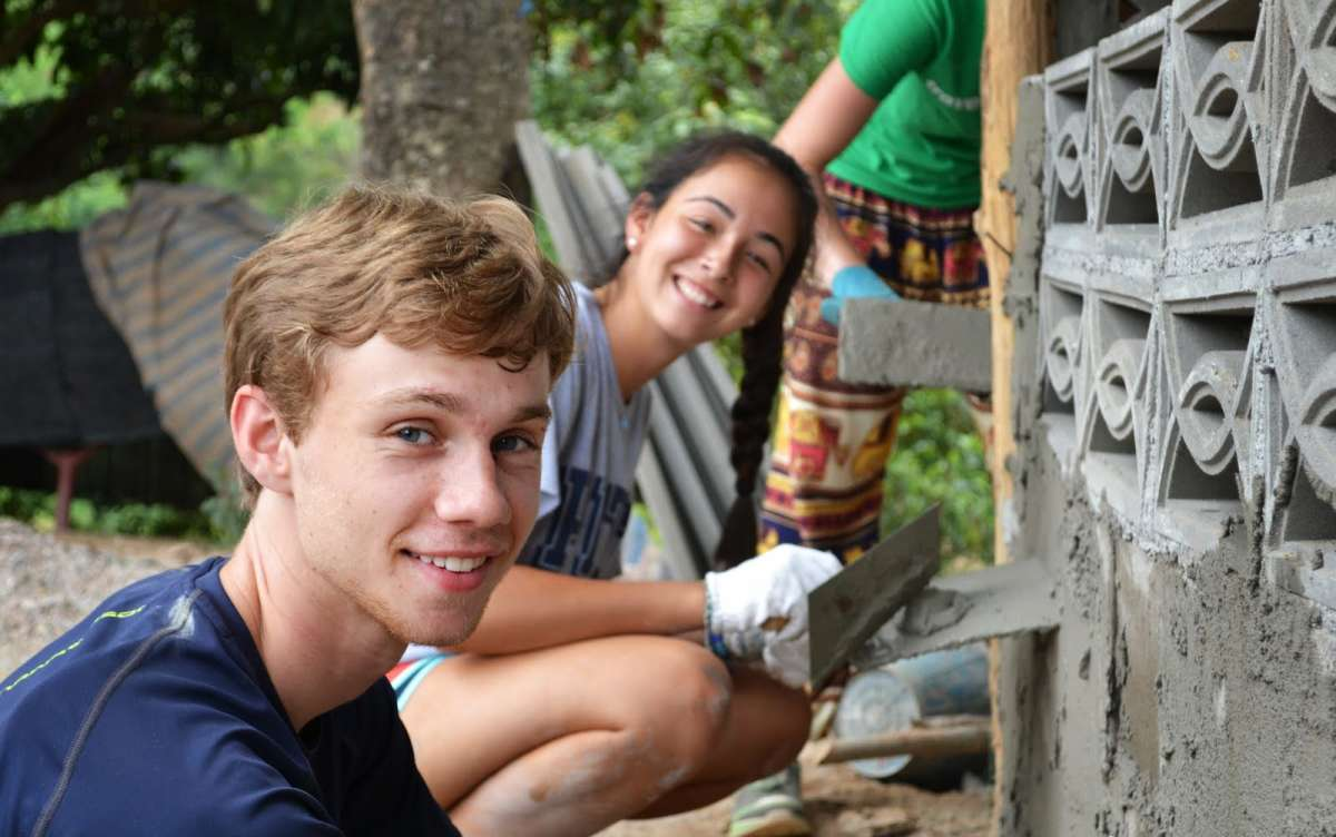 Teenage travelers volunteering doing community service during summer youth travel program in Thailand