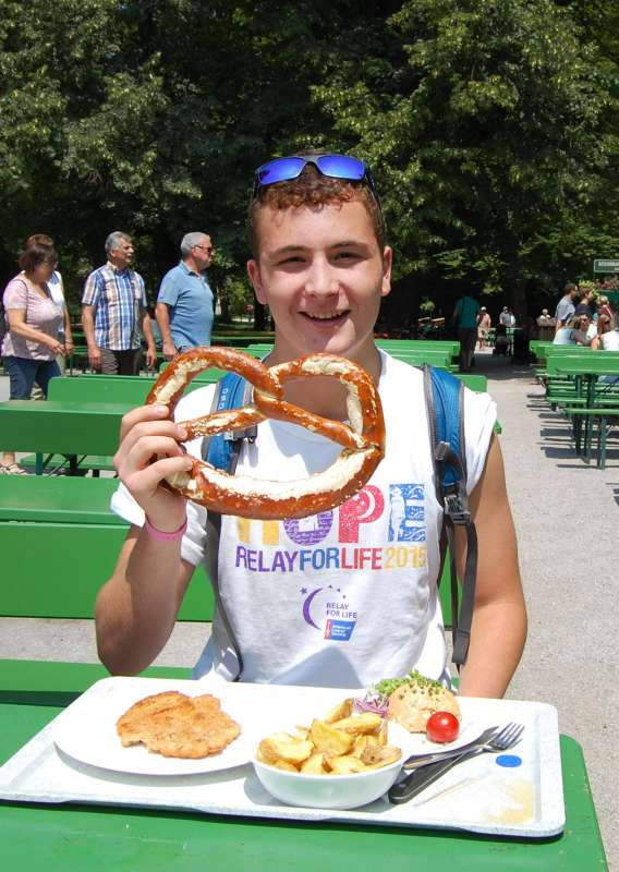Teen eats authentic local cuisine in Munich Bavaria on summer adventure youth program