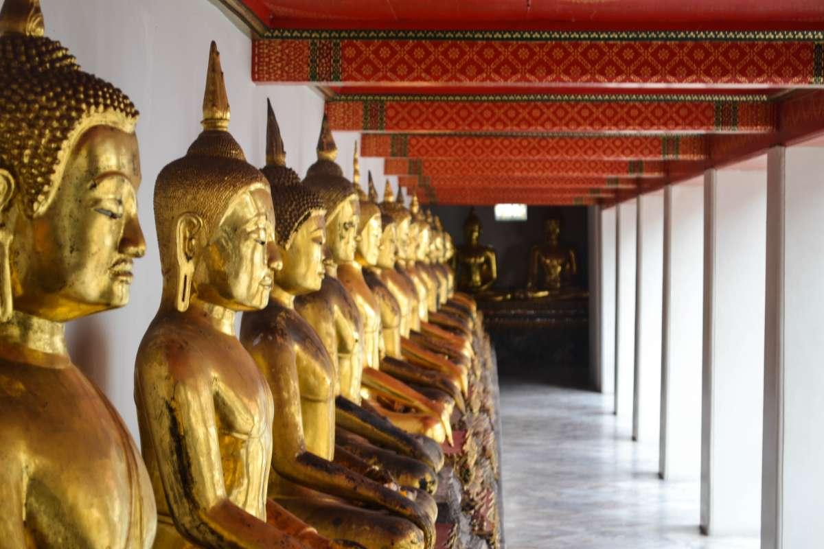 Golden Buddha statues seen by teenage travelers during summer youth travel program in Thailand