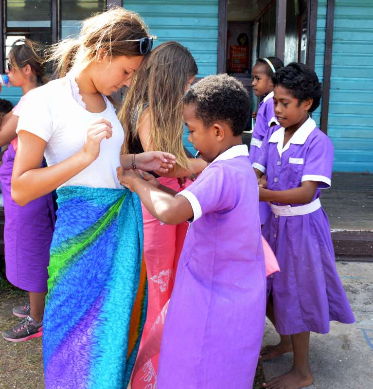 Fijian children help American girl tie her skirt during summer youth program in Fiji