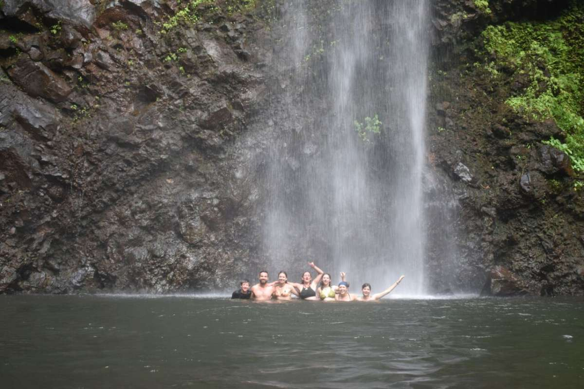 Teens swim under a waterfall on service and adventure program in Hawaii.