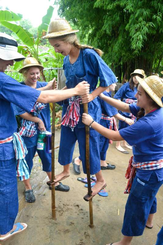 Teenage travelers play on stilts during summer youth travel program in Thailand