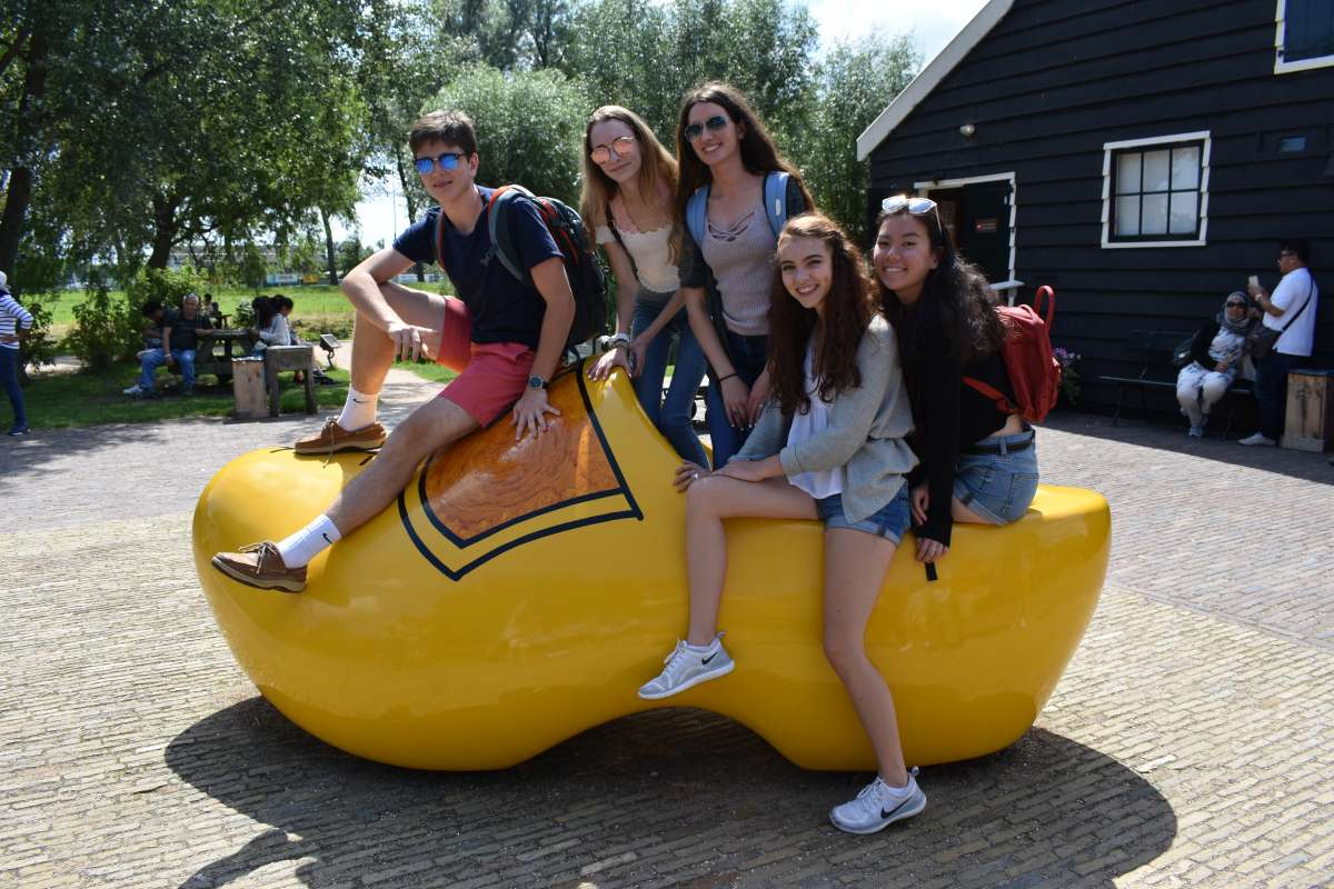 Teen travelers visit traditional Dutch village with wooden clogs on summer travel program