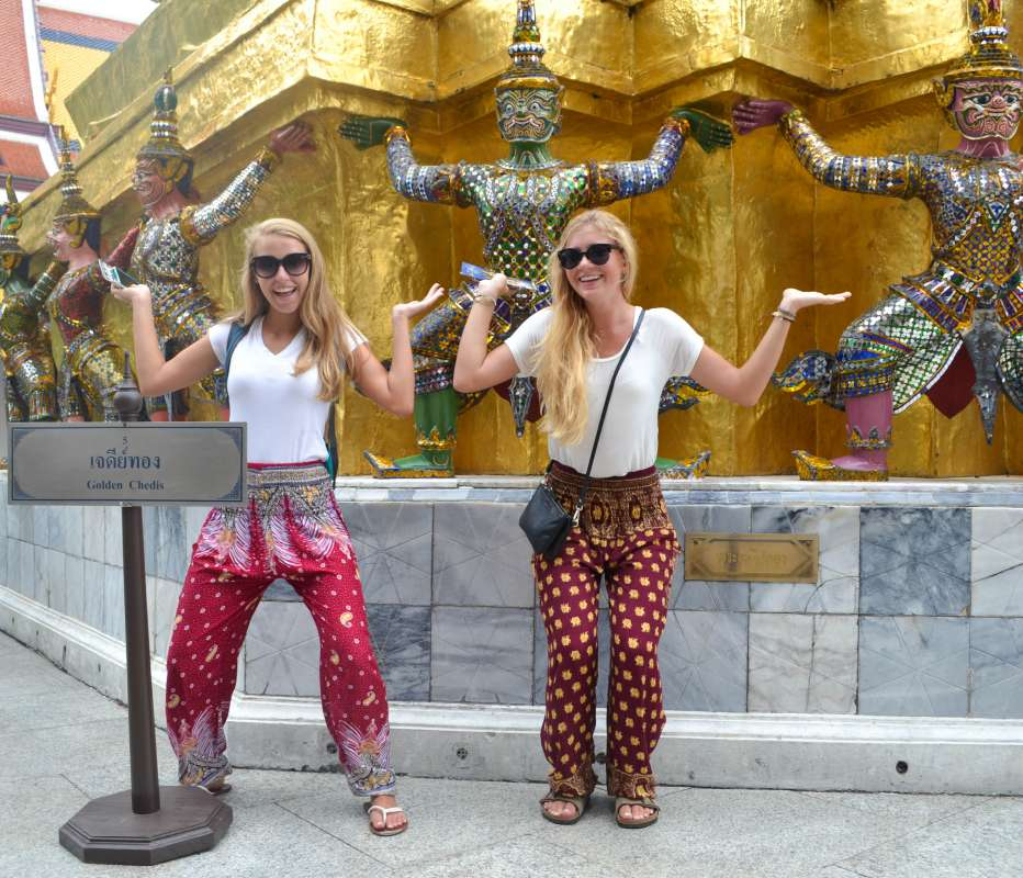 Teenage travelers wearing elephant pants have fun next to statues during summer youth travel program in Thailand