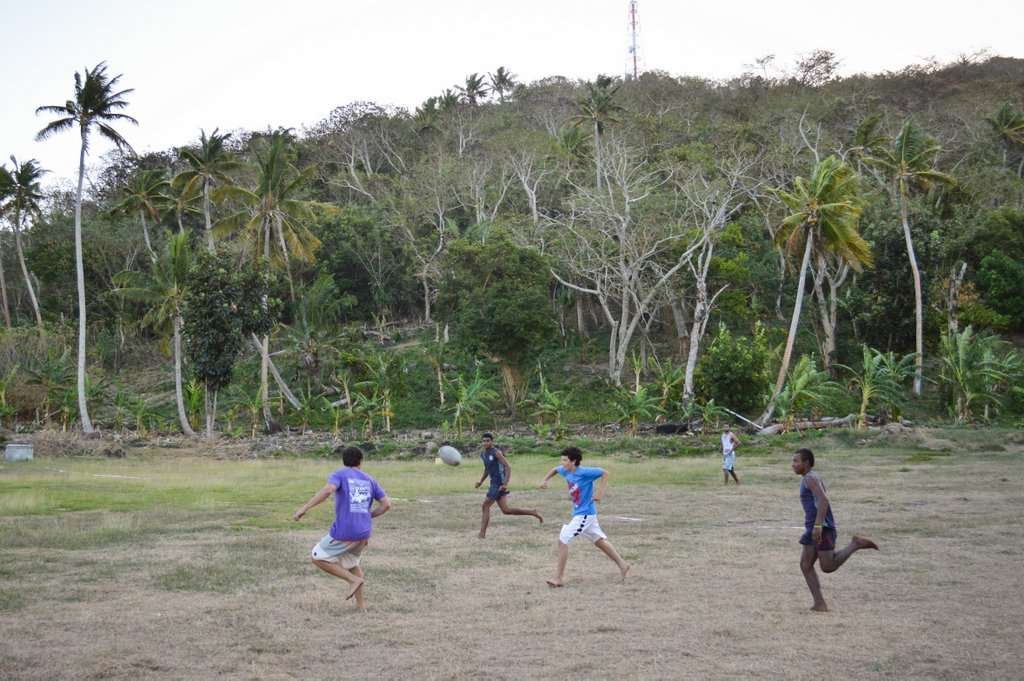 Teenage traveler plays soccer with Fijian schoolchildren during summer youth program in Fiji