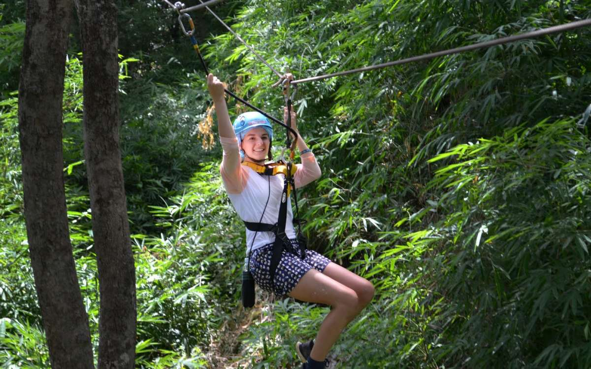 Teenage traveler does zipline tour during summer youth travel program in Thailand