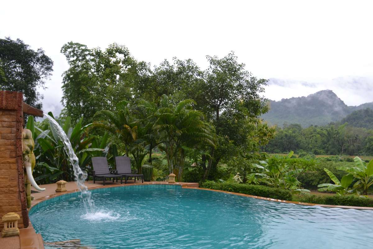 Pool and waterfall and mountains seen by teenage travelers during summer youth program in Southeast Asia