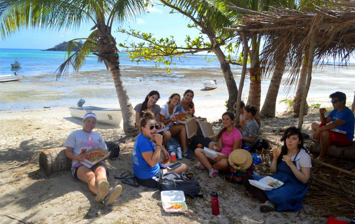 Teen travelers lounge on the beach on their summer high school program to Fiji.
